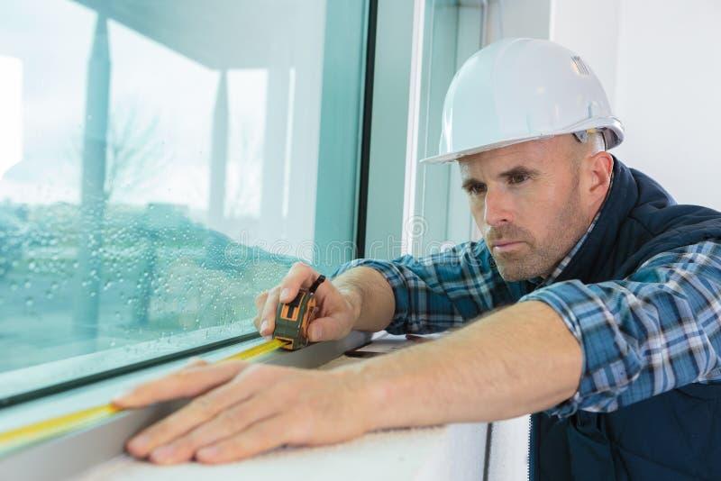 Arbeider die venster meten bij bouwwerf royalty-vrije stock afbeeldingen