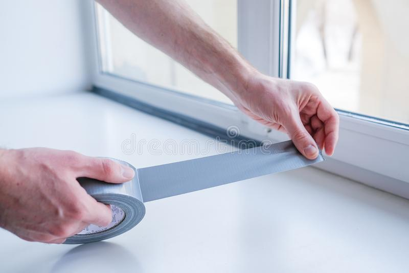 Arbeider die verzegelende band op venster binnenshuis zetten royalty-vrije stock foto