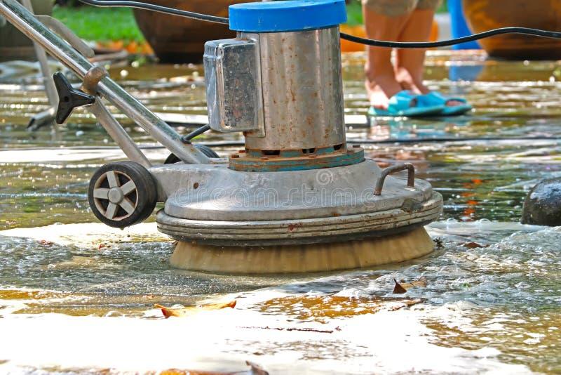 Arbeider die vuile vloer met machinereinigingsmachine schoonmaakt royalty-vrije stock foto's