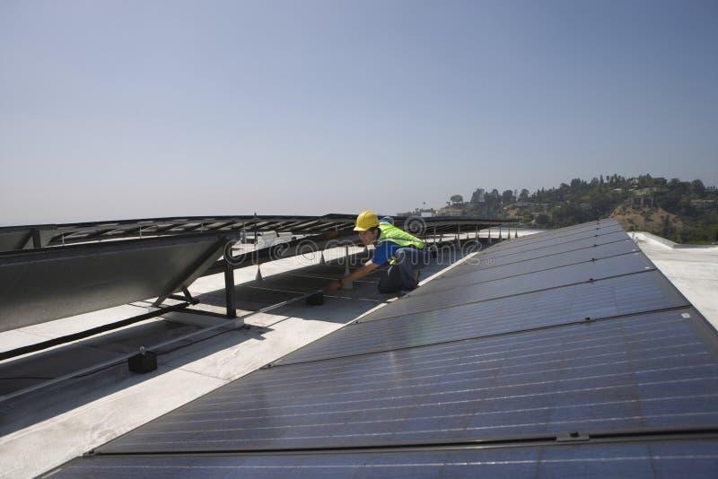 Arbeider die Zonnepanelen controleren op Dak royalty-vrije stock afbeelding