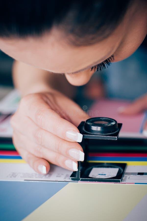 Arbeider in druk en pers centar gebruik een vergrootglas stock foto