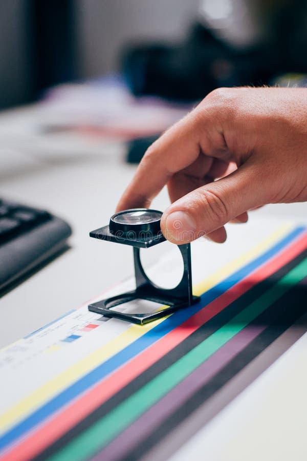 Arbeider in druk en pers centar gebruik een vergrootglas stock fotografie