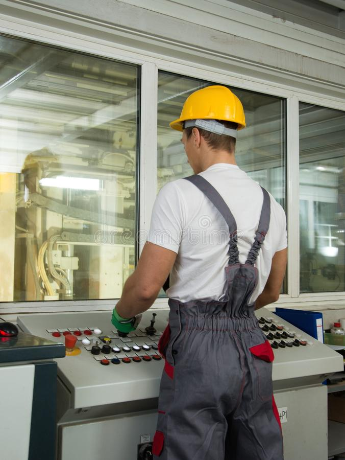 Arbeider in een fabriekscontrolekamer stock foto's