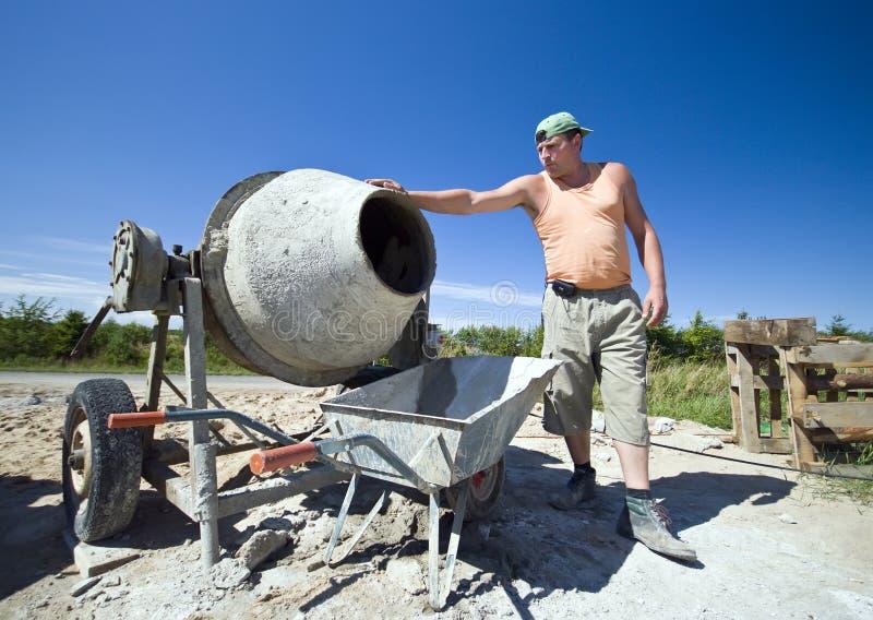 Arbeider en concrete mixer stock afbeeldingen