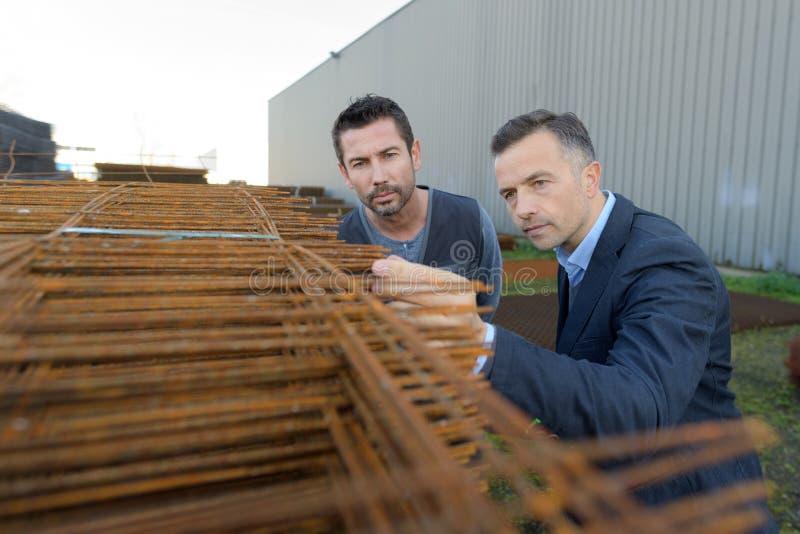 Arbeider en manager die concrete versterkingsstukken inspecteren bij yard royalty-vrije stock afbeelding