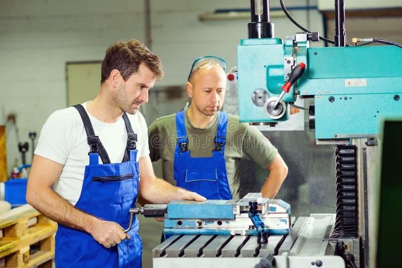 Arbeider in fabriek op de machine stock afbeeldingen