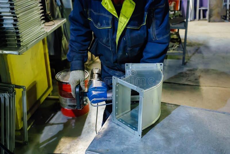 Arbeider in het metaalbewerkende installatie installeren klinknagels in deel voor bouwbuizen door pneumatische klinkhamer te gebr royalty-vrije stock foto