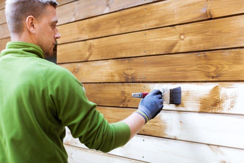 Arbeider het schilderen huis buiten met houten beschermende kleur stock afbeeldingen