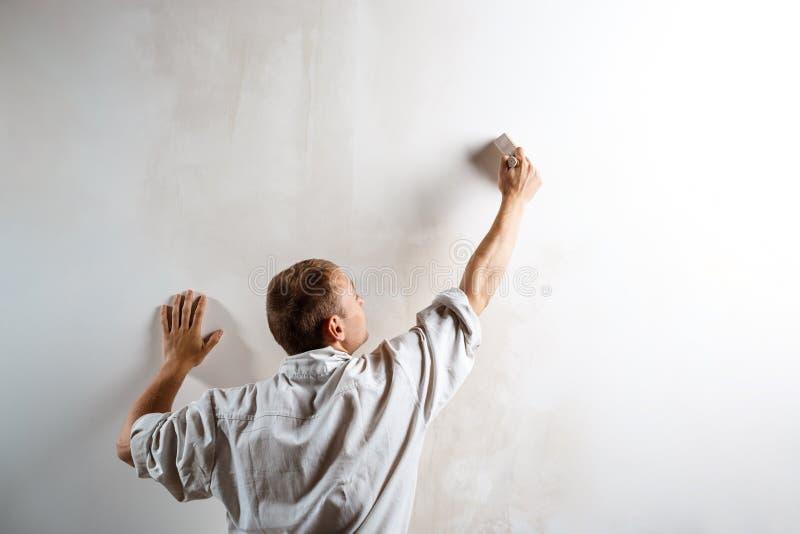 Arbeider het schilderen muur met borstel in witte kleur De ruimte van het exemplaar royalty-vrije stock foto
