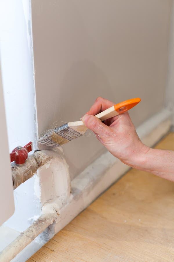 Arbeider het schilderen muur in ruimte Het schilderen van muren in een hoek met een verfborstel royalty-vrije stock foto