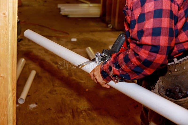 Arbeider in het zagen van pvc-pijpen, het proces van de de Industriebouw om knipsel voor te bereiden stock afbeelding