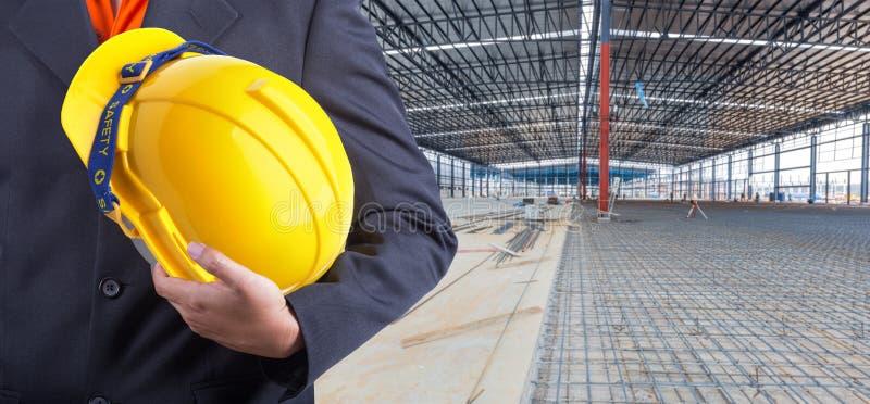 Arbeider of ingenieursholding in handen gele helm stock afbeeldingen