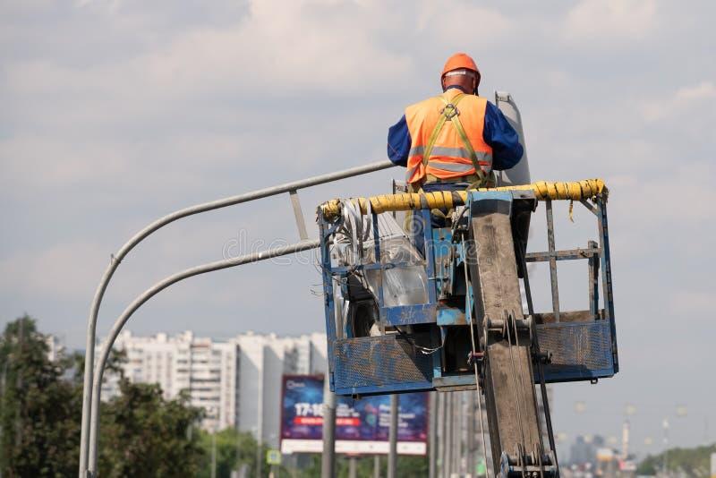 Arbeider in liftemmer tijdens installatie van metaalpool met straatlantaarn, straatlantaarnpool met dubbel hoofd stock afbeeldingen