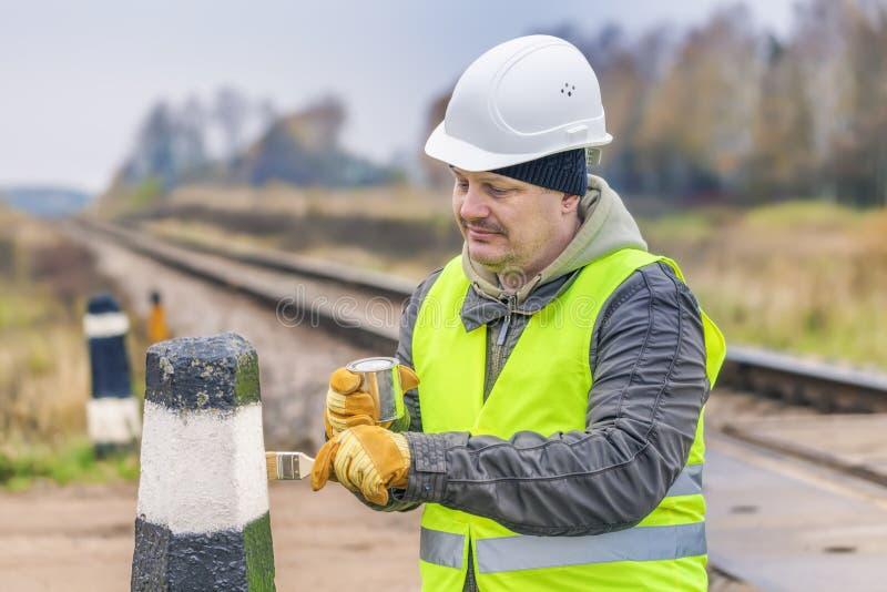 Arbeider met borstel en verf op de spoorweg stock fotografie