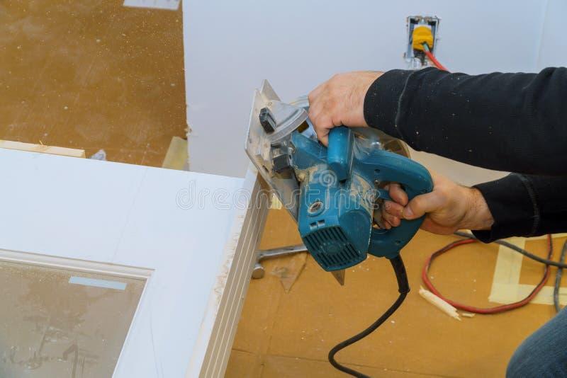 Arbeider met cirkelzaagmachine bij het snijden van houten deur royalty-vrije stock foto