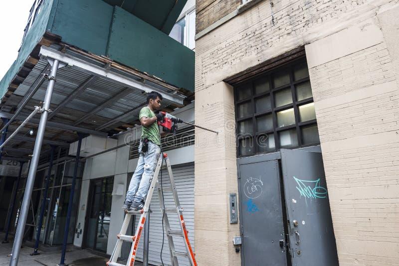 Arbeider met een boor die een gat in de muur in de Stad van New York, de V.S. maken stock afbeeldingen