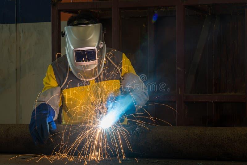 Arbeider met het beschermende metaal van het maskerlassen in fabriek royalty-vrije stock afbeeldingen