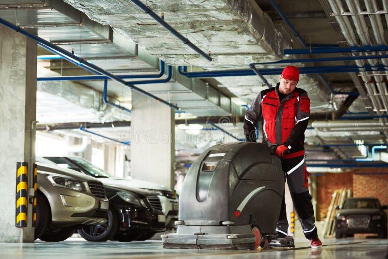 Arbeider met machine schoonmakende vloer in parkerengarage royalty-vrije stock fotografie