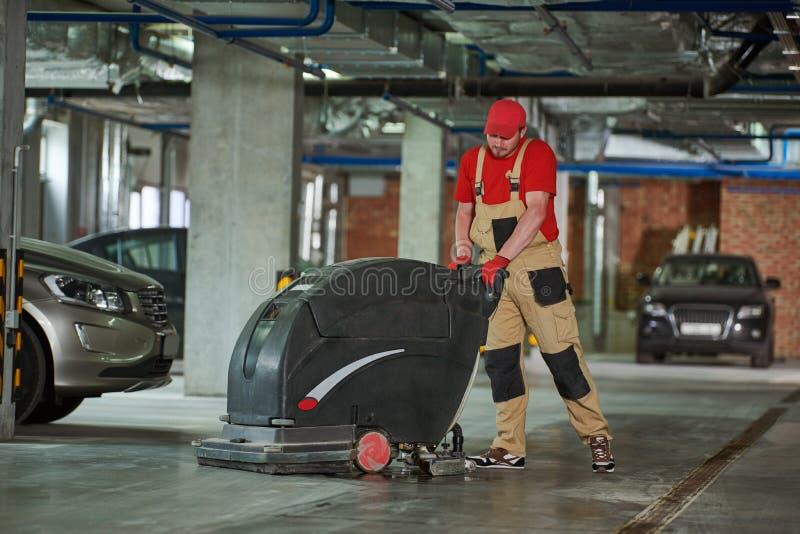Arbeider met machine schoonmakende vloer in parkerengarage stock afbeelding