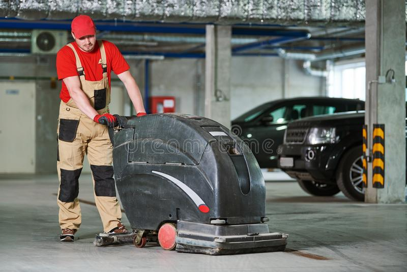 Arbeider met machine schoonmakende vloer in parkerengarage royalty-vrije stock afbeelding