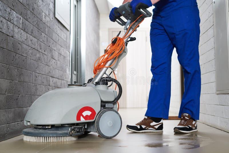 Arbeider met machine schoonmakende vloer in woonplaatszaal royalty-vrije stock foto