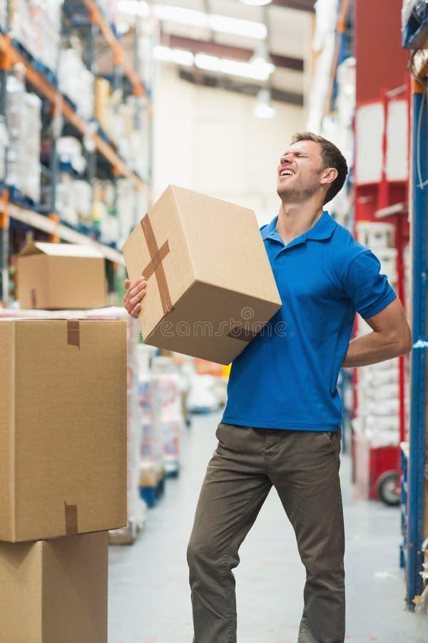 Arbeider met rugpijn terwijl het opheffen van doos in pakhuis stock afbeeldingen