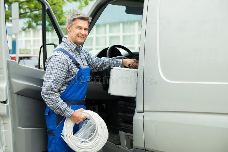 Arbeider met Toolbox en Kabel die in Bestelwagen binnengaan stock foto's