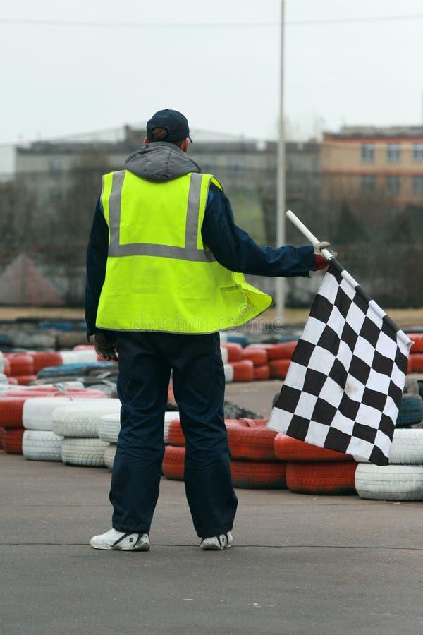 Arbeider met vlag bij gaan-kar het rennen stock afbeelding