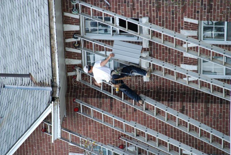 Arbeider op een ladder stock afbeelding