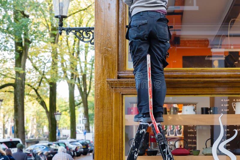 Arbeider op een ladder voor een winkel royalty-vrije stock fotografie