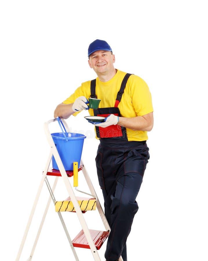 Arbeider op ladder met kop thee royalty-vrije stock afbeeldingen