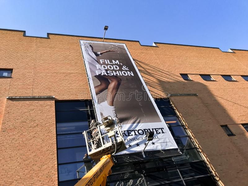 Arbeider op lift die omhoog reuze reclameaffiche bij de wandelgalerijbouw hangen stock afbeelding