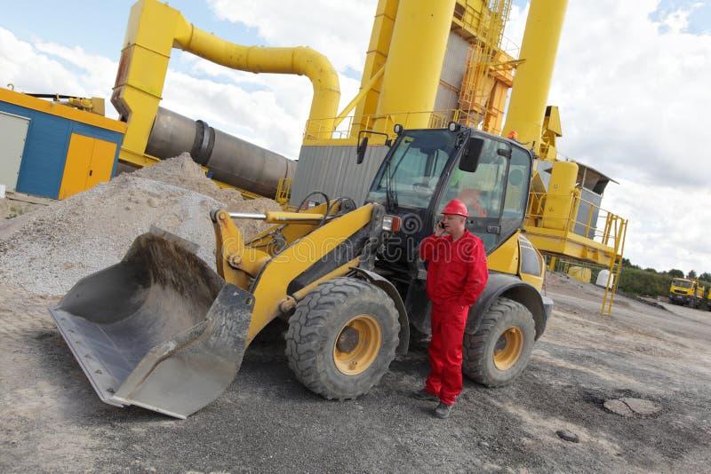 Arbeider in rode eenvormig op telefoon bij buldozer bij bouwwerf stock fotografie