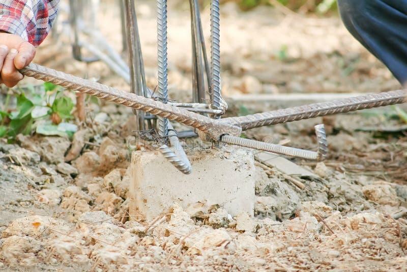 Arbeider twee die staalhulpmiddel om staal door zijn hand met behulp van voor te buigen maakt omheiningsbouw royalty-vrije stock foto's