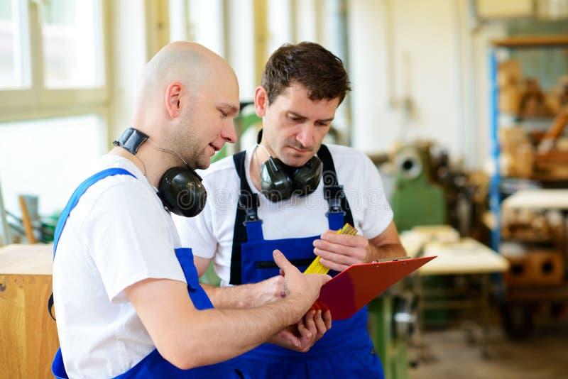 Arbeider twee in een timmermans` s workshop in gesprek royalty-vrije stock afbeelding