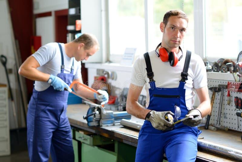 Arbeider twee op het werkbank in fabriek stock fotografie