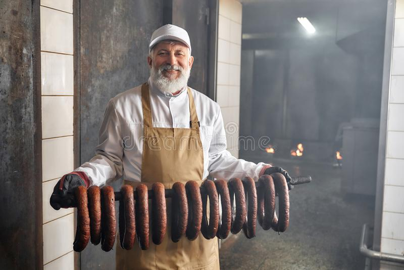 Arbeider van rookhokholding gerookte worsten, het stellen stock afbeeldingen