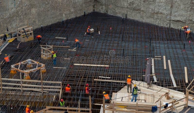 Arbeiders aan het werk voor de bouw van de gewapend beton basis royalty-vrije stock afbeelding