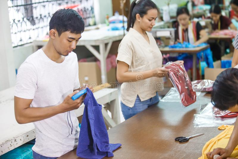 Arbeiders bij de textielbedrijf etikettering van, en de verpakking van hun produc royalty-vrije stock foto's