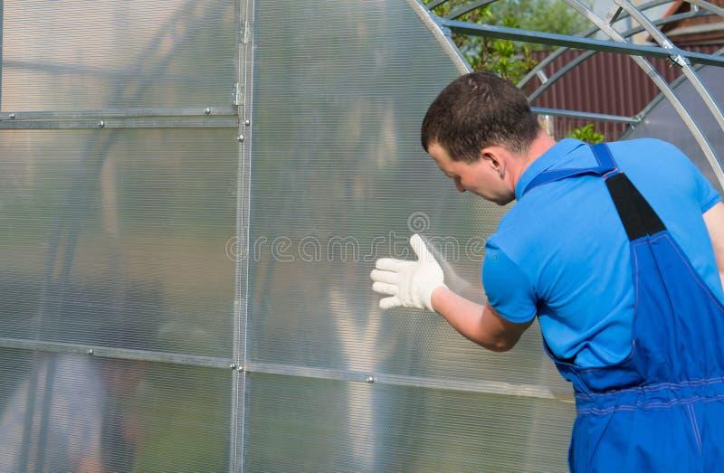 Arbeiders in blauwe uniformen, die de correcte installatie van de serre en het polycarbonaat controleren op het stock afbeelding