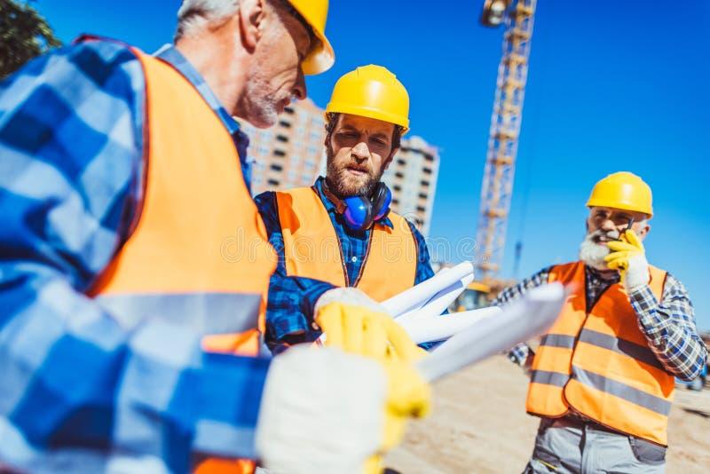 Arbeiders in bouwvakkers en vesten die de bouwplannen onderzoeken terwijl status royalty-vrije stock afbeeldingen