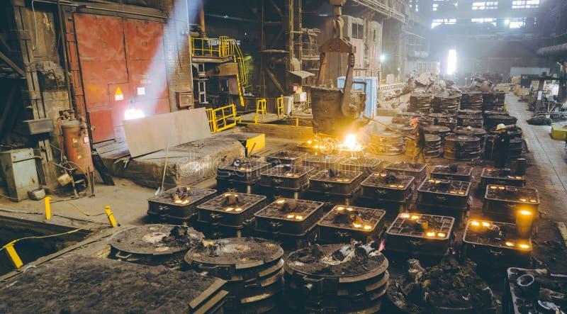 Arbeiders controlerend smelten van metaal in ovens stock afbeeldingen