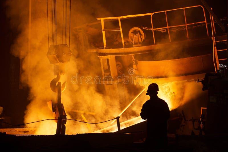 Arbeiders controlerend smelten van metaal in ovens stock afbeelding