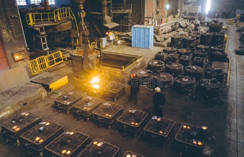 Arbeiders controlerend smelten van metaal in ovens royalty-vrije stock afbeelding