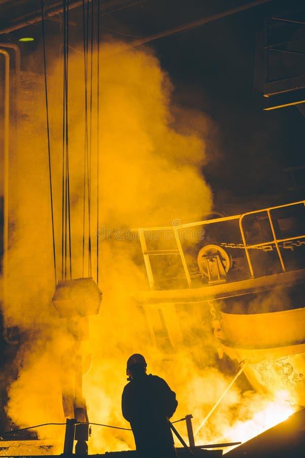 Arbeiders controlerend smelten van metaal in ovens stock fotografie