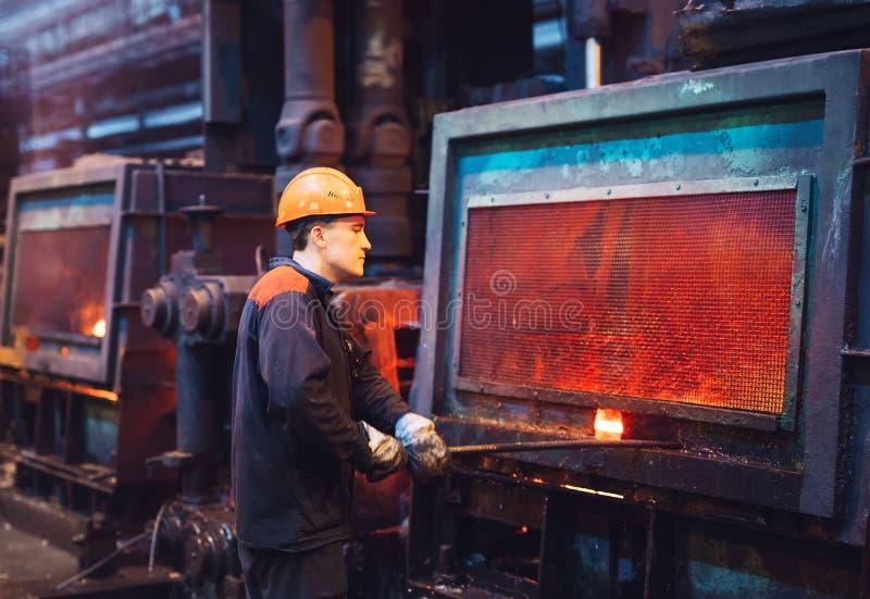 Arbeiders in de staalfabriek De fabrieksarbeider neemt een steekproef voor metaal stock afbeelding
