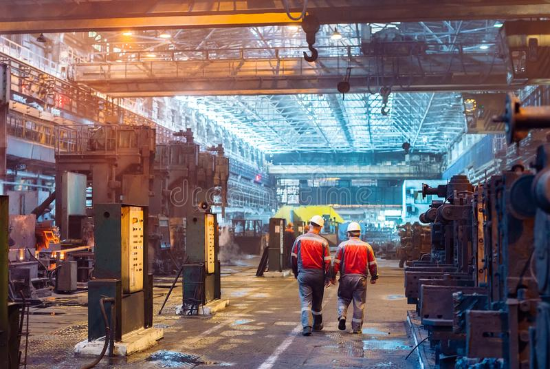 Arbeiders in de staalfabriek De fabrieksarbeider neemt een steekproef voor metaal stock afbeeldingen