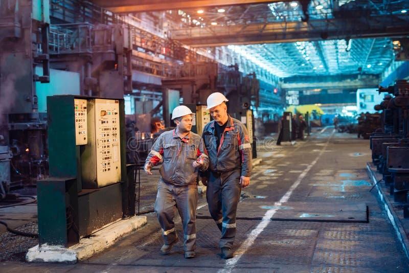 Arbeiders in de staalfabriek De fabrieksarbeider neemt een steekproef voor metaal royalty-vrije stock fotografie
