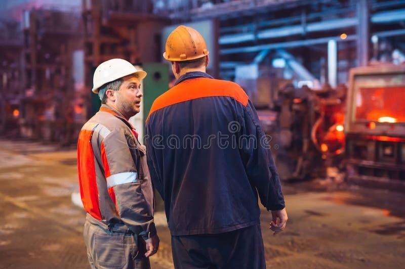 Arbeiders in de staalfabriek op de metallurgische installatie stock foto