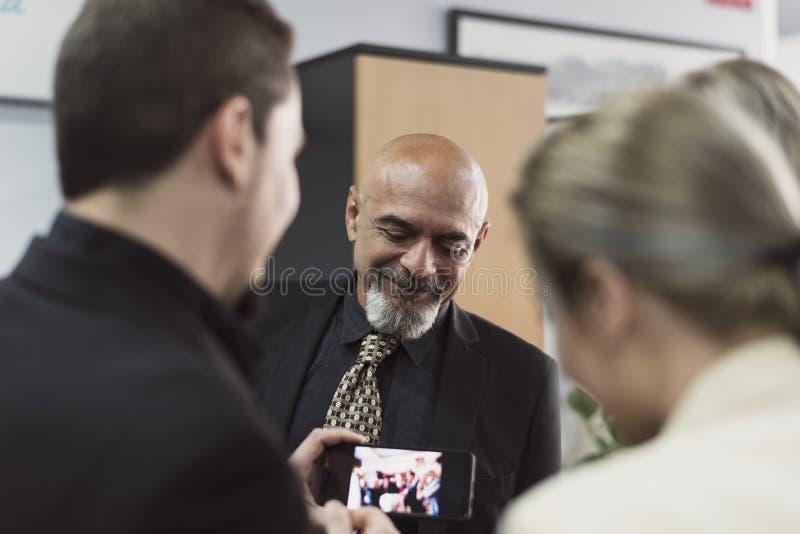 Arbeiders die in bureau iets in smartphone kijken stock afbeelding